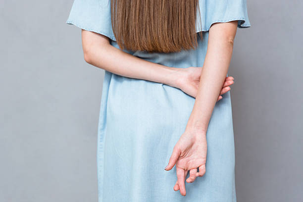 close up of crossed fingers behind woman's back - delude stock pictures, royalty-free photos & images
