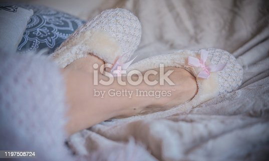 Close Up of  Crossed Woman Feet in Fluffy Slippers on the Bed