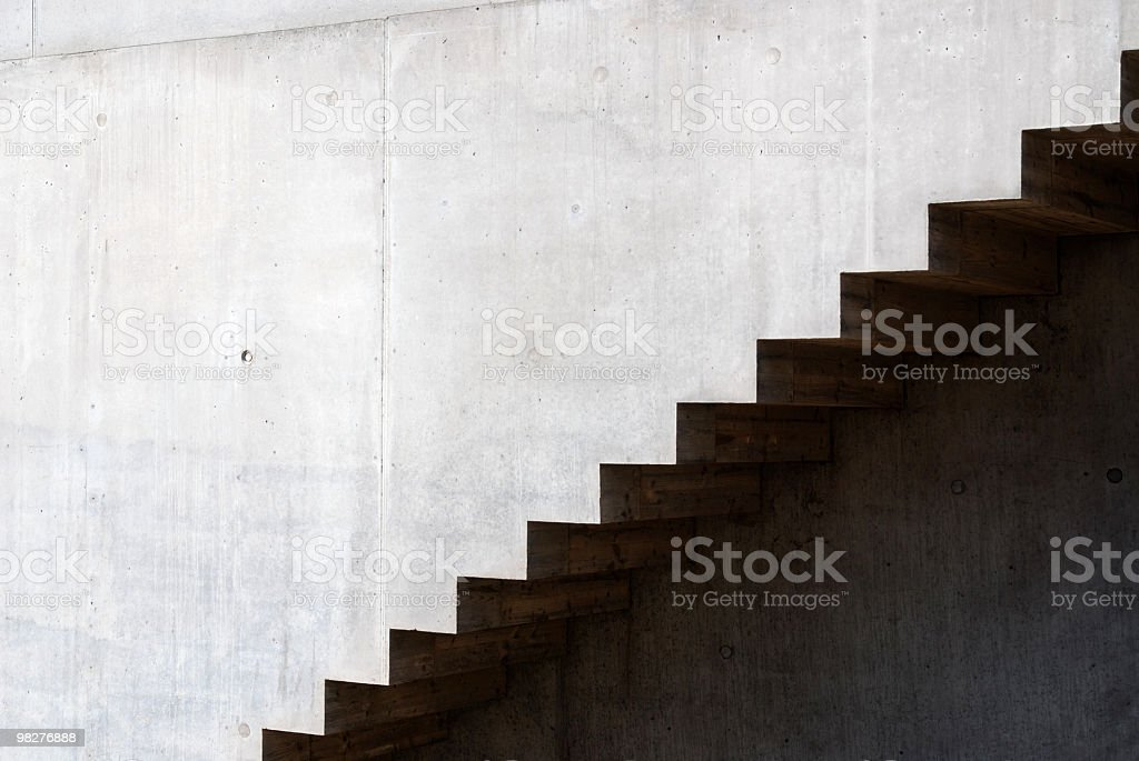Close up of dark stairs against a light concrete wall royalty-free stock photo
