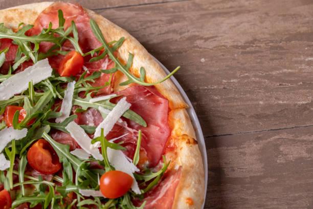close up of delicious italian fresh pizza with ham, arugula, tomato and parmesan - bresaola foto e immagini stock