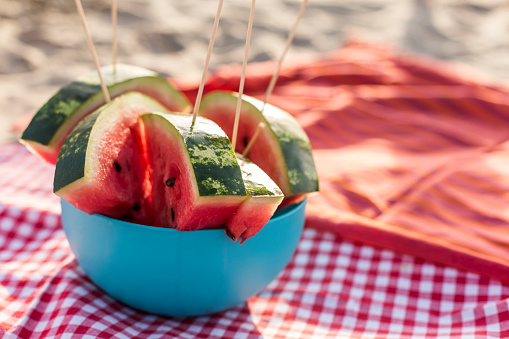 Copy space shot of delicious, juicy watermelon slices on a stick, arranged in a bowl, laying on a picnic blanket at the beach in warm summer sunshine.