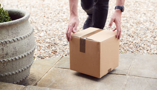 Close Up Of Delivery Driver Putting Package On Doorstep Outside House stock photo
