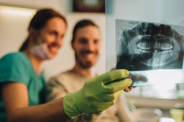 Close up of dentist and patient examining Orthopantogram. stock photo