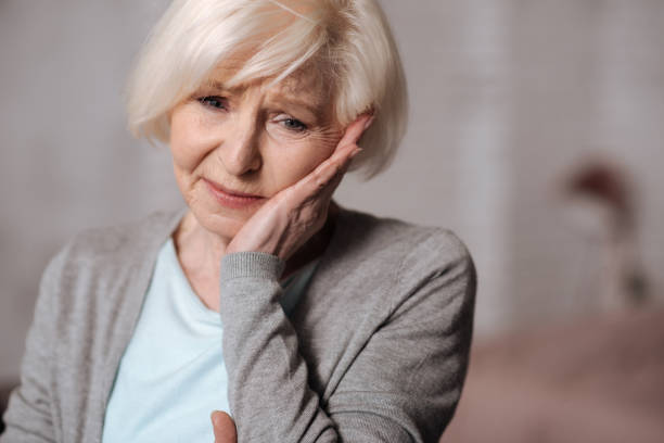 Close up of depressed aged woman So unexpected. Close up portrait of very depressed senior lady touchig her cheeck with hand. toothache stock pictures, royalty-free photos & images