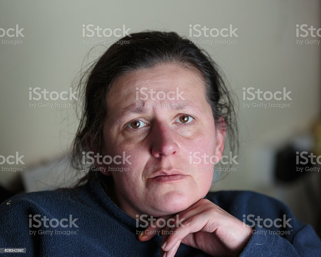 Close up of depressed looking middle aged woman, unprocessed stock photo