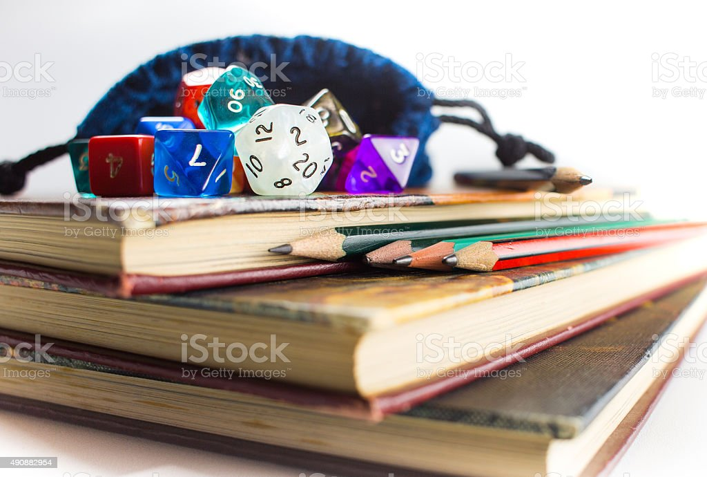 Close up of Dice and Pencils on top of Books stock photo