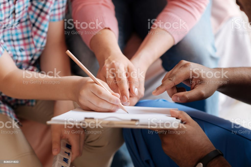 Close up of different hands that pointing at paper stock photo