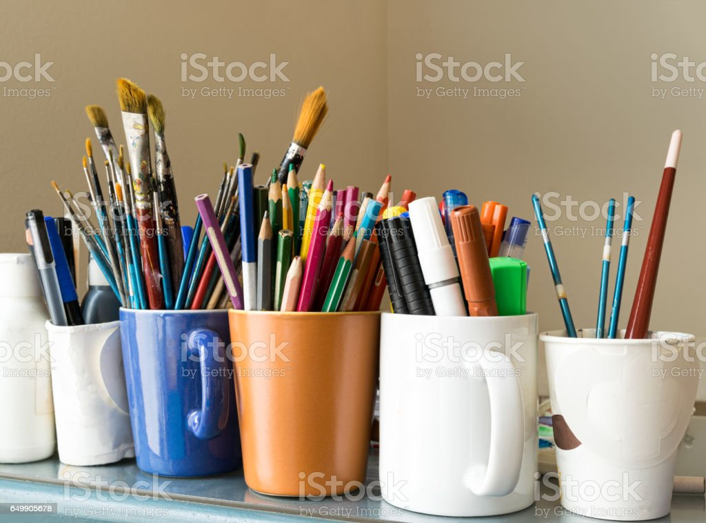 Close up of different used paint brushes, sharpened colored pencils, pens, and markers stock photo