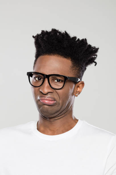 Close up of disgusted afro american man Close up portrait of disgusted afro american man on gray background. African guy with funky hairstyle wearing white t-shirt and nerdy eyeglasses. disgust stock pictures, royalty-free photos & images