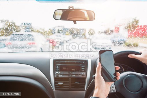 527894422istockphoto Close Up of Distracted Driver Using Mobile Phone While Driving With Oncoming Traffic 1174007846