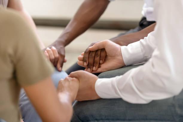 il primo tempo di persone diverse si tiene per mano durante la sessione di terapia - assuefazione foto e immagini stock