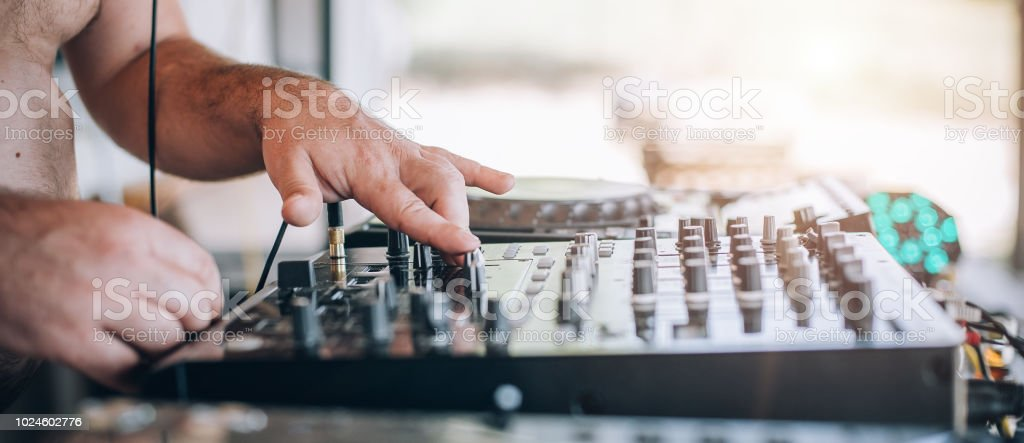close up of dj hands plays music on player and mixer stock photo