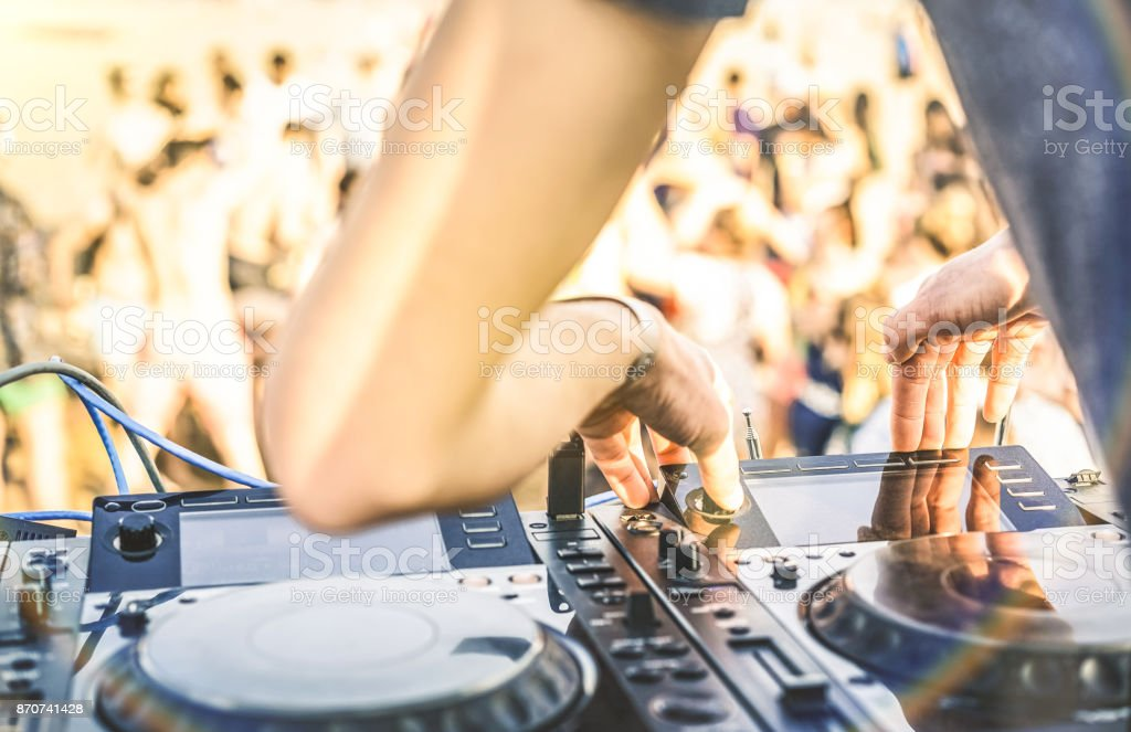 Close up of dj playing electro sound on modern cd usb player at summer beach party - Music festival and entertainment concept  - Defocused background with shallow depth of field - Focus on mixing hand royalty-free stock photo