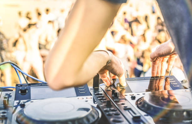Close up of dj playing electro sound on modern cd usb player at summer beach party - Music festival and entertainment concept  - Defocused background with shallow depth of field - Focus on mixing hand stock photo