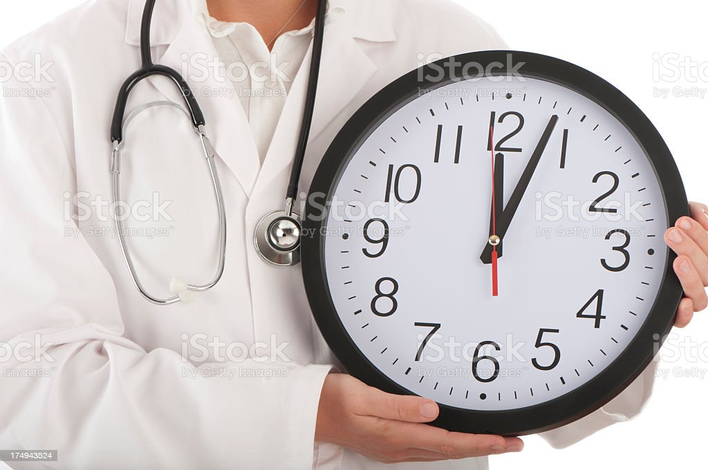 Close up of doctor holding a clock stock photo