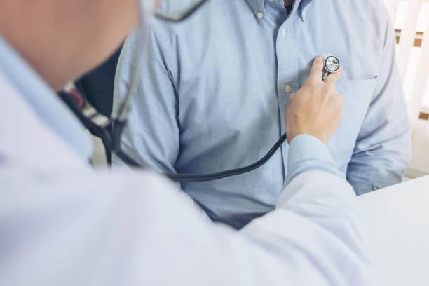 Close-up de médico ouvir batimentos cardíacos de pacientes com estetoscópio no conceito de hospital, exame físico, médico e cuidados de saúde - foto de acervo