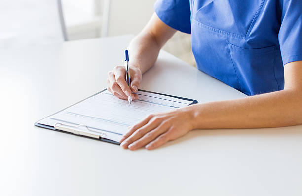 close up of doctor or nurse writing to clipboard stock photo
