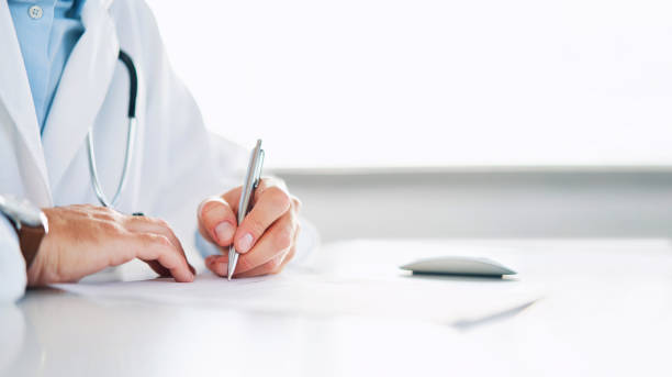 Close up of doctor signing prescription for patient stock photo