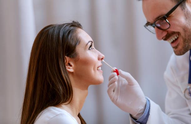 Close up of doctor taking sample from nose. Selective focus on smiling female patient. Close up of doctor taking sample from nose. Selective focus on smiling female patient. nose stock pictures, royalty-free photos & images
