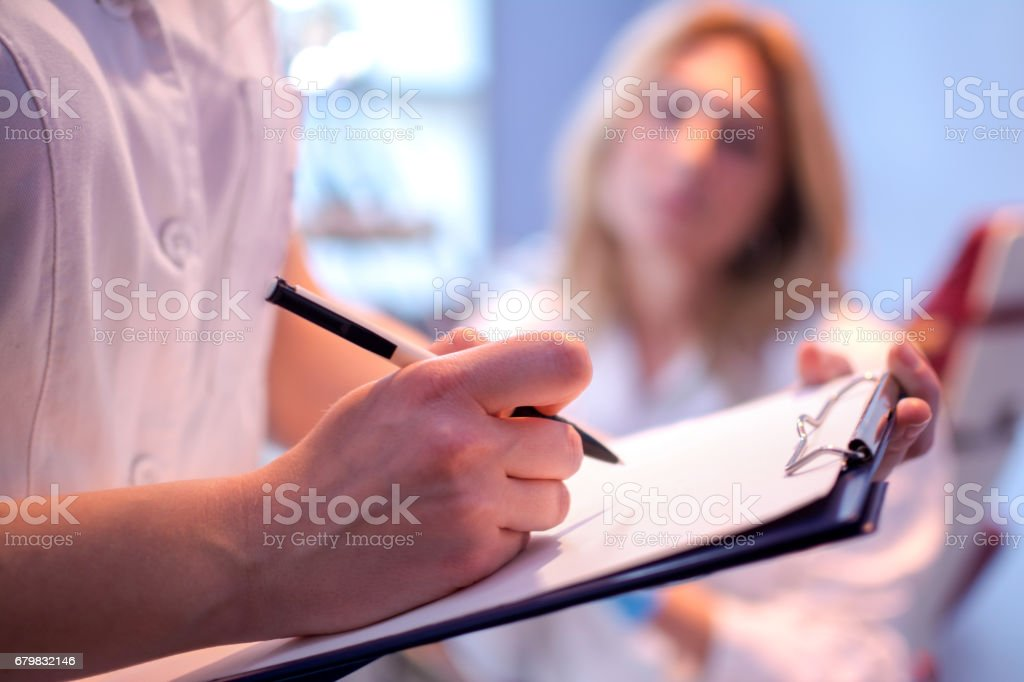 Close up of doctor writing on a medical chart. royalty-free stock photo