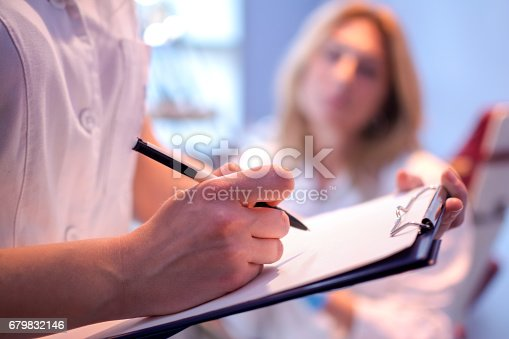 istock Close up of doctor writing on a medical chart. 679832146