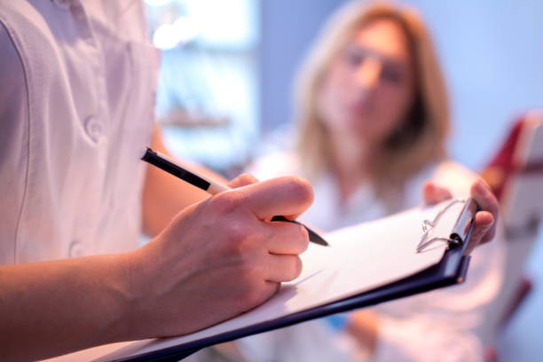 Close up of doctor writing on a medical chart. stock photo