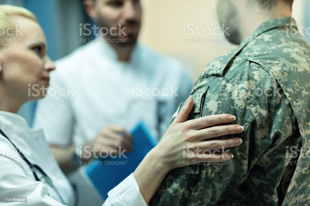Close up of army soldier being consoled while talking with doctors at...