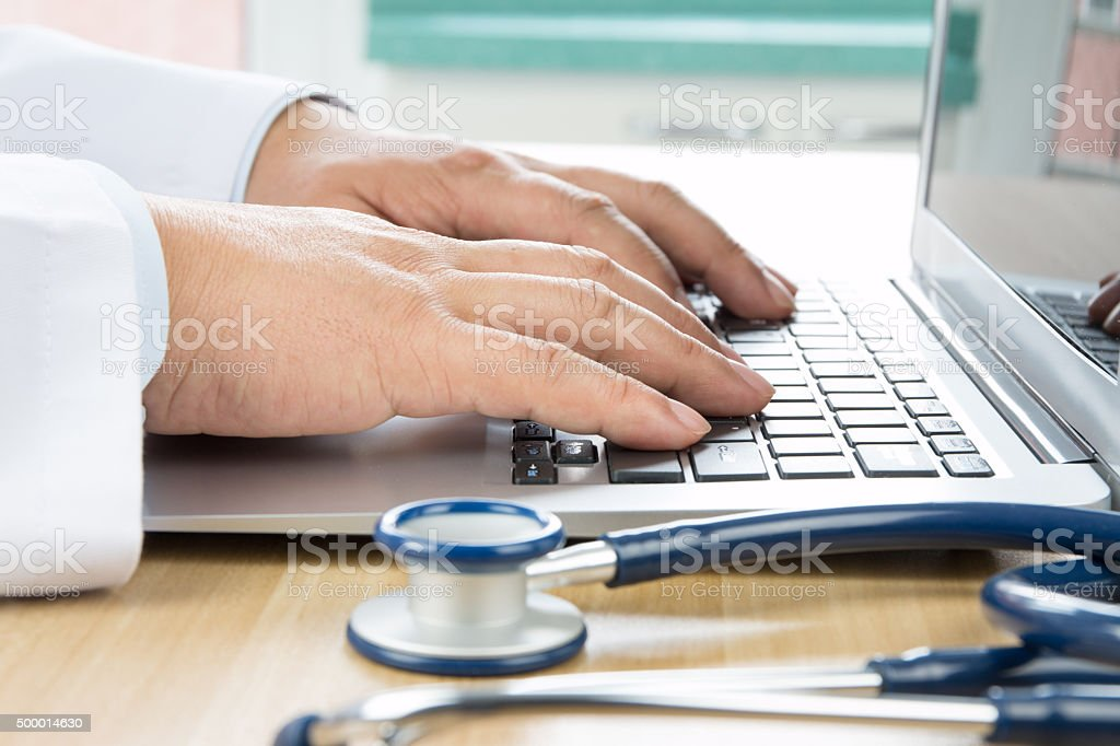 Close up of doctor's hand at computer typing stock photo