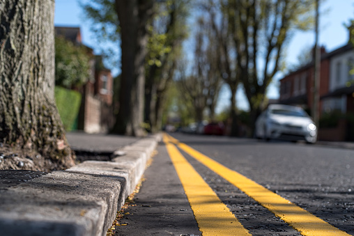 Close up of double yellow lines (meaning, no parking at any time) at the curb of a tree lined residential urban street, Belfast, Northern Ireland.