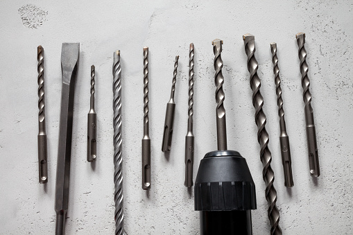 Close up of drill bits on concrete background. This file is cleaned and retouched.