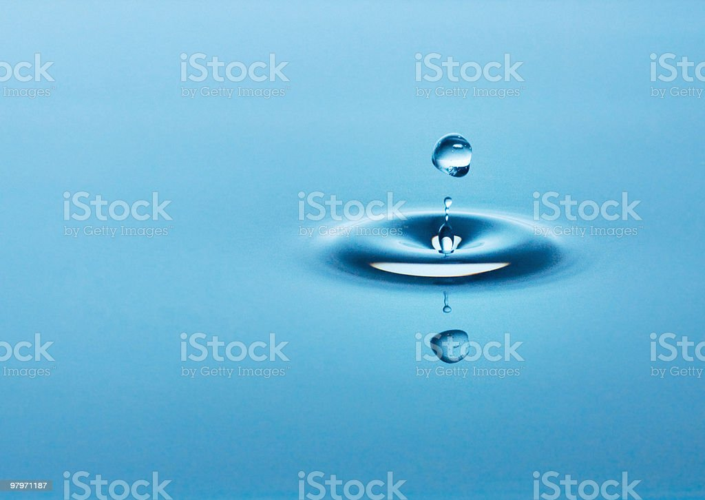 Close up of droplet falling in pool of water royalty-free stock photo