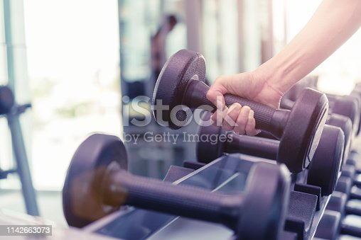 Close up of dumbbell in fitness gym sport complex. Sport, healthy life and lifestyle concept.