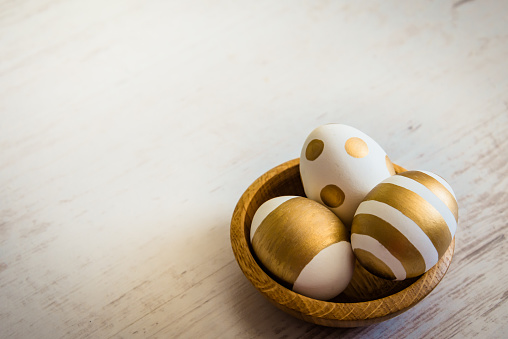 Close up of easter eggs colored with golden paint in a wooden plate. Various striped and dotted designs. White wooden background.
