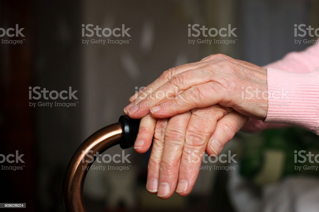 Close up of elderly woman holding a walking cane in nursing home. stock photo