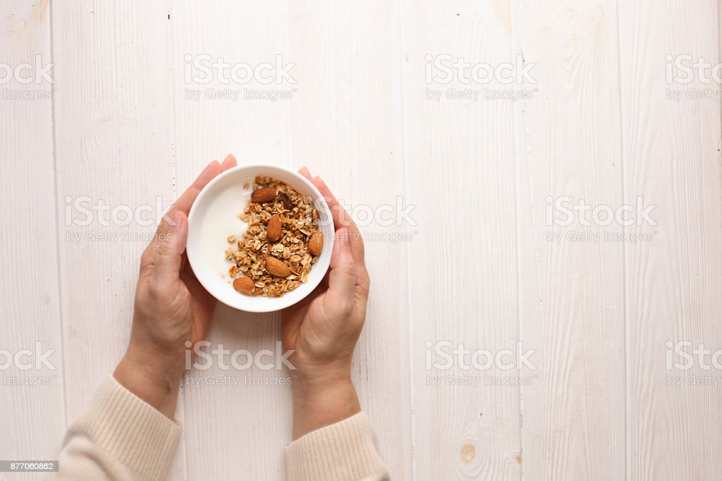 A close up of elderly woman in beige cardigan holding a bowl of sugar free granola superfood cereal with greek yogurt, wrinkled hands, soft daylight stock photo