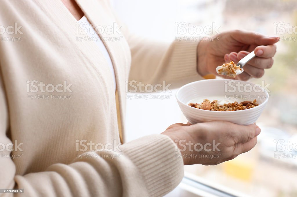 A close up of elderly woman in beige cardigan standing near the window holding a bowl of sugar free granola superfood cereal with greek yogurt, wrinkled hands, soft daylight stock photo