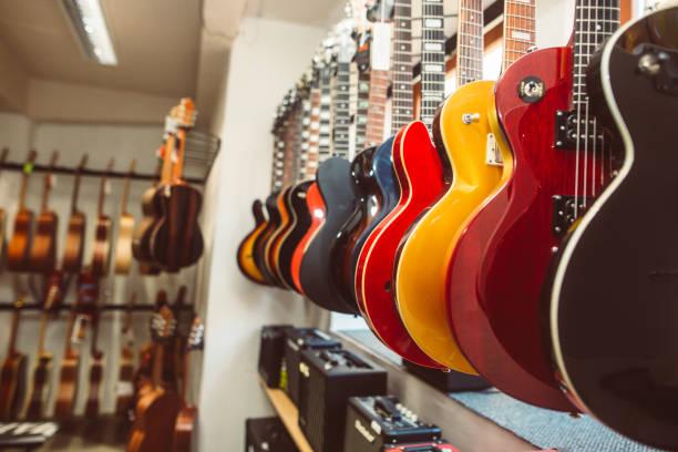 zbliżenie gitar elektrycznych z rzędu w ogromnym sklepie z instrumentami, koncepcja instrumentalna muzyki - instrument muzyczny zdjęcia i obrazy z banku zdjęć