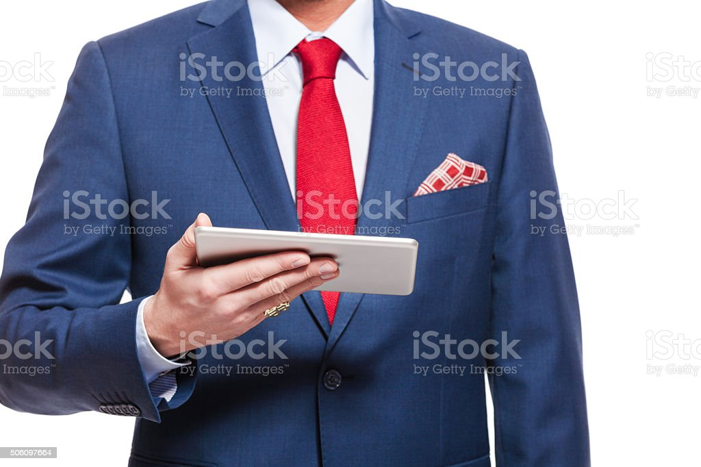 Close up of elegant businessman wearing suit, holding digital tablet Elegant businessman wearing suit, red tie and pocket square, holding a digital tablet. Close up of hand and torso, unregoznizable person. Adult Stock Photo