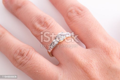 Close up of elegant diamond ring on the finger with white background. Diamond ring.