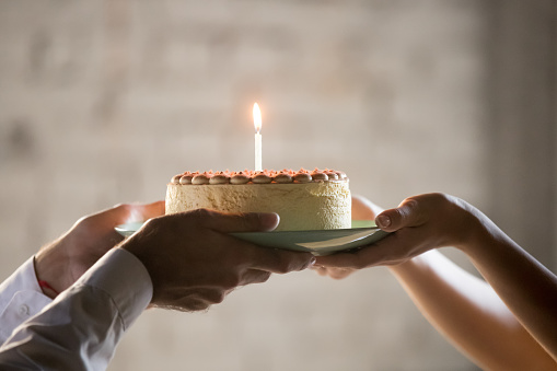istock Close up of employee presenting cream pie with candle 1129819951