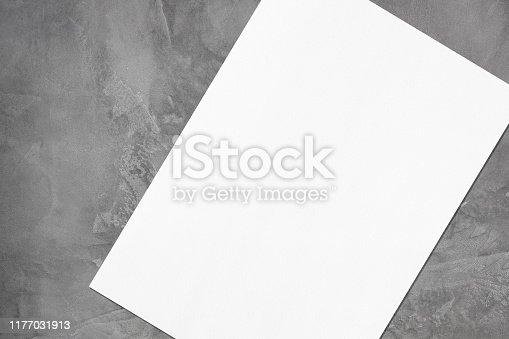 1171907064 istock photo Close up of empty white rectangle poster mockup lying diagonally on grey concrete background 1177031913