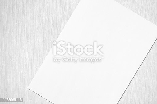 1173565159 istock photo Close up of empty white rectangle poster or card mockup lying diagonally on neutral light grey textured background 1173565113