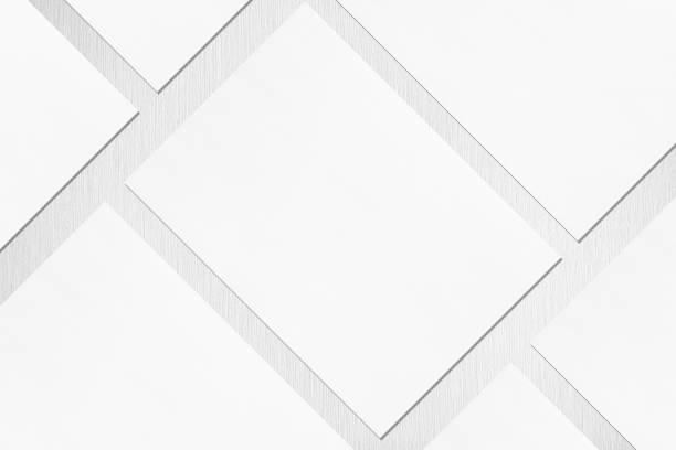 fermez-vous vers le haut de l'affiche ou des maquettes blanches vides de rectangle se trouvant en diagonale sur le fond texturé gris clair - business card mock up photos et images de collection