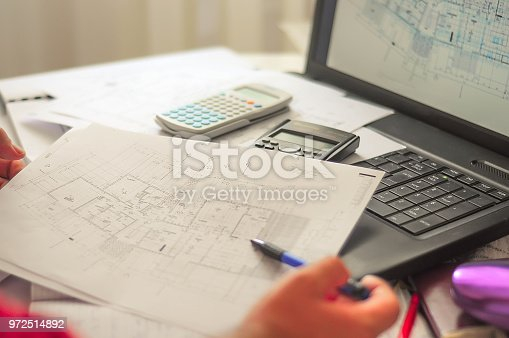 638881988istockphoto Close up of engineers hands working on table, he drawing project sketch in construction site or office 972514892