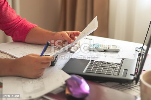 638881988istockphoto Close up of engineers hands working on table, he drawing project sketch in construction site or office 972515038