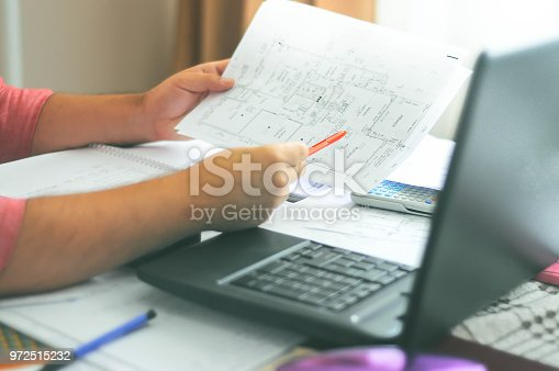 638881988istockphoto Close up of engineers hands working on table, he drawing project sketch in construction site or office 972515232