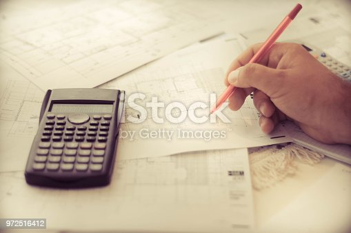 638881988istockphoto Close up of engineers hands working on table, he drawing project sketch in construction site or office 972516412
