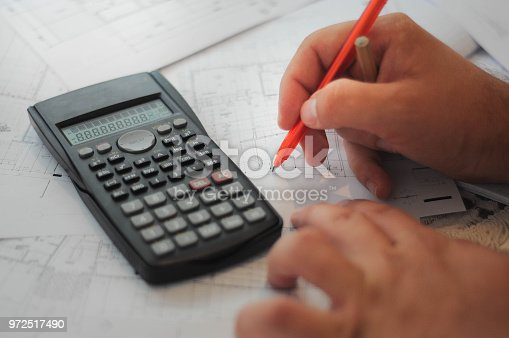 840610244istockphoto Close up of engineers hands working on table, he drawing project sketch in construction site or office 972517490