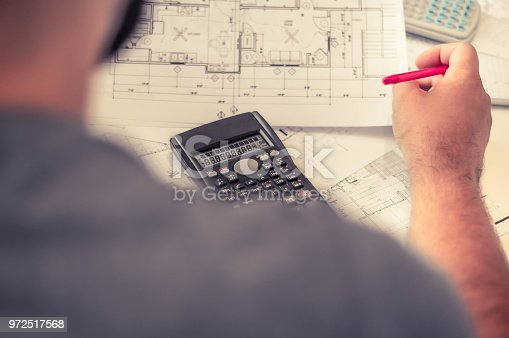 638881988istockphoto Close up of engineers hands working on table, he drawing project sketch in construction site or office 972517568