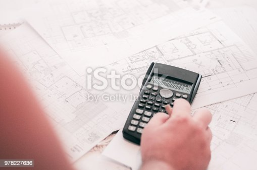 638881988istockphoto Close up of engineers hands working on table, he drawing project sketch in construction site or office 978227636